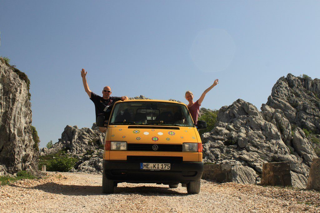 Gelber Volkswagen Transporter mit Silke und Jan, die heraus hängen