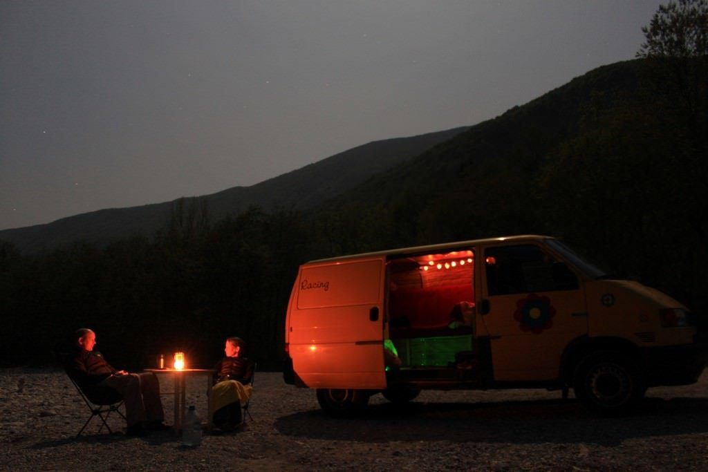 Silke und Jan sitzen abends vor ihrem Van