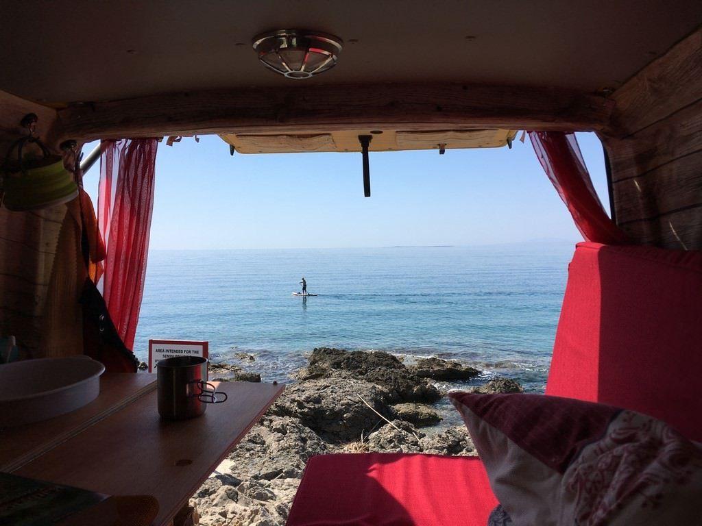 Vom Bus aus in Richtung Meer schauen. Jemand surft.