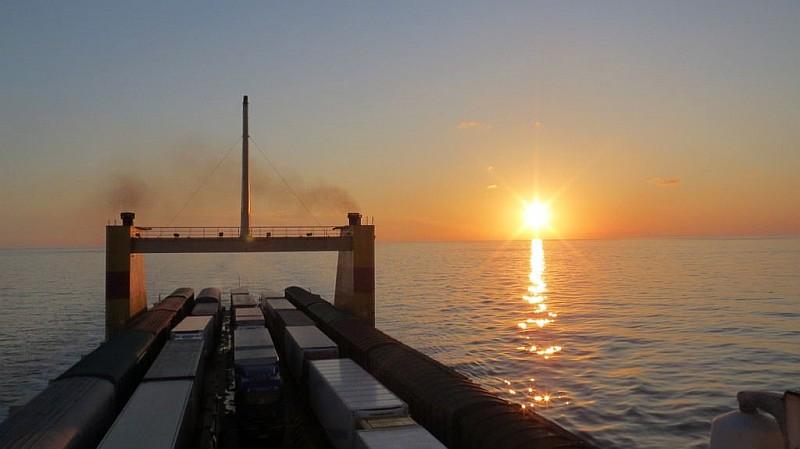 Frachtschiff in Meer mit Sonnenuntergang