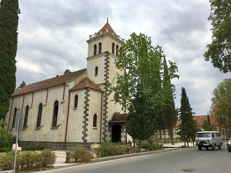 Straße mit Kirche und altem russischem Lieferwagen