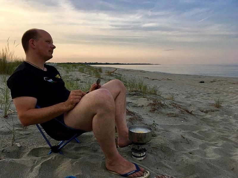 Jan sitzt auf eine Kopie des beliebten Helinox Campingsessels und schaut sich das Meer an