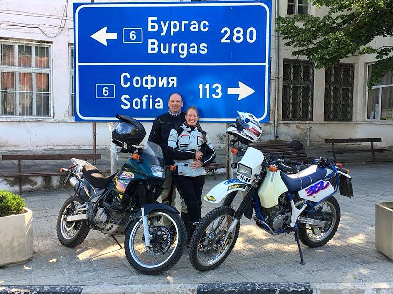 Silke und Jan mit ihren Motorrädern vor einem bulgarischen Straßenschild